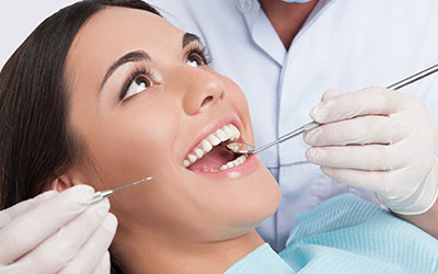 Attractive woman in dental chair under examination by dentist